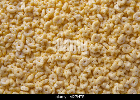 Background of cornflakes in the form of rings and stars, closeup. Food backdrop - Stock Photo