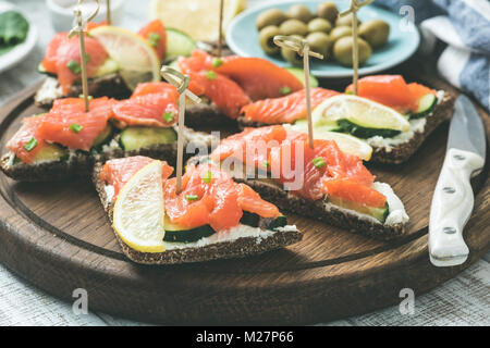 Salmon canape with cream cheese on wooden board. Selective focus, toned image - Stock Photo