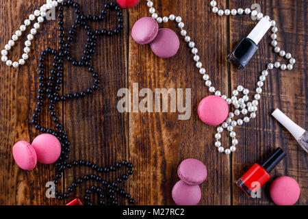 Gentle biscuits macaroons on a wooden background with the attributes of a women's handbag. View from above. - Stock Photo
