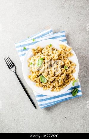 Vegan dinner. Farfalle pasta with pesto sauce and basil leaves on white plate, grey stone background, copy space - Stock Photo