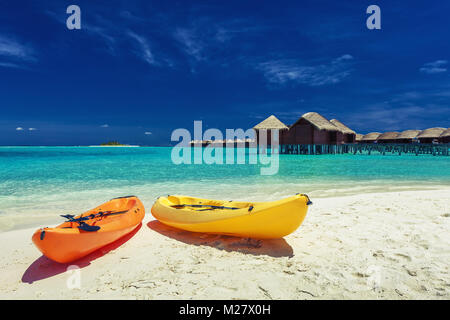 Yellow and orangel kayaks on the tropical beach with villas in background - Stock Photo