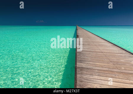 Wooden long jetty over lagoon with amazing clean azure water, Maldives - Stock Photo