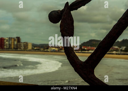 Landscape with old huge anchor in front of the beach of Saint Lorenzo in Gijon, Asturias, Spain. Old anchor made - Stock Photo
