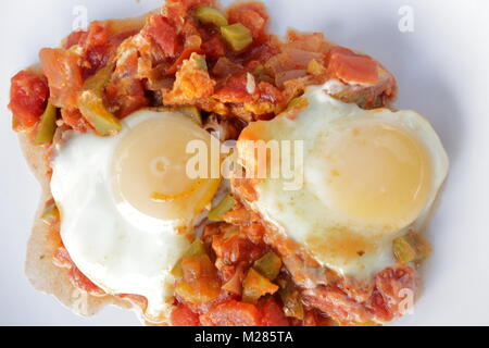 Shakshouka, a popular Middle Eastern dish originating in Tunisia, made of onion, tomato, capsicum, garlic and eggs - Stock Photo