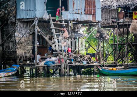 Children climbing ladder to house on stilts, Kampong Phluk Floating Village, Siem Reap Province, Cambodia. - Stock Photo
