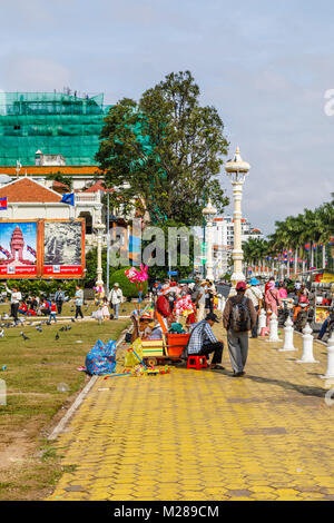 Yellow pavement of the bustling popular waterfront Sisowath Quay promenade by Royal Palace Park, Phnom Penh, capital - Stock Photo