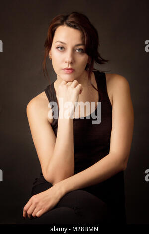 Portrait of a young beautiful brunette woman in studio - Stock Photo