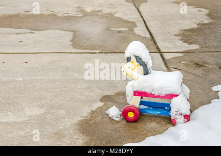 Plastic toy horse left outside and covered with snow - Stock Photo