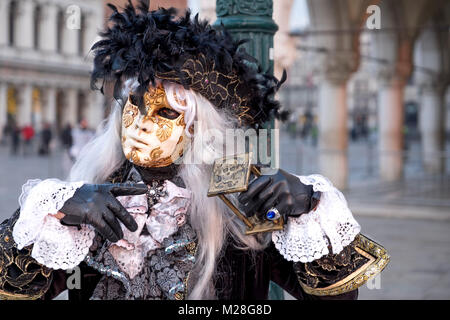 VENICE, ITALY - FEBRUARY 04: People wearing carnival costumes pose in San Marco square on February 4, 2018 in Venice, - Stock Photo