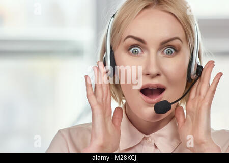 Portrait of extremely surprised woman with headset. Excited woman with headset opens mouth widely being shocked - Stock Photo