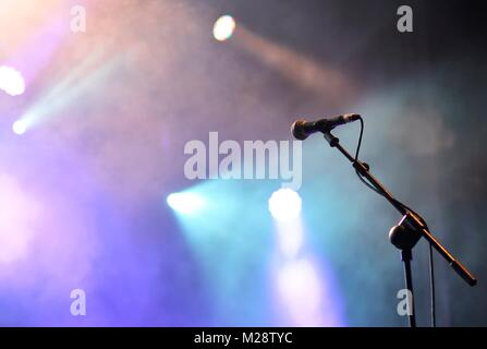 Microphone with spotlights with colored lights at a rock concert. - Stock Photo