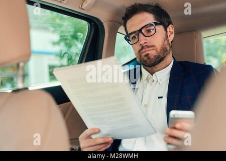 Young businessman reading paperwork and using a cellphone while sitting in the backseat of a car being driven through - Stock Photo