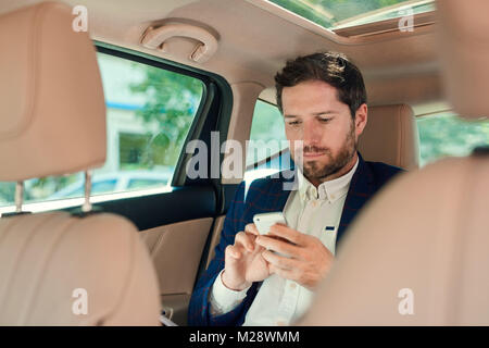 Young businessman sending a text message on a cellphone while sitting in the backseat of a car driving through the - Stock Photo