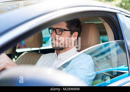 Young man wearing glasses smiling while sitting behind the wheel of his car driving through the city - Stock Photo