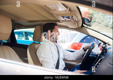 Smiling young man sitting in his car driving through the city during his morning commute - Stock Photo