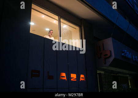 May 17, 2016 - Athens, Greece - A man looks out of a window of City Plaza Hotel in Athens. The hotel, abandoned - Stock Photo