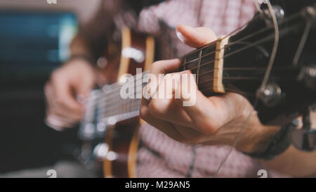 Male musician plays the guitar, hands close up - Stock Photo