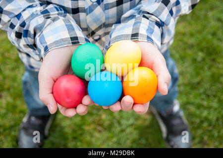 Easter hunt - colorful eggs in child hands - Stock Photo