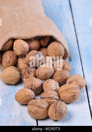 Walnuts on wooden table in the kitchen. - Stock Photo