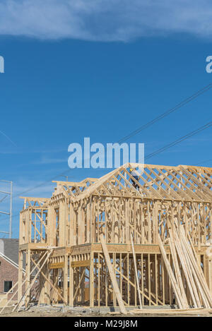 Wood frame house under construction with builder roofing. New two-story stick built next to completed homes in Irving, - Stock Photo