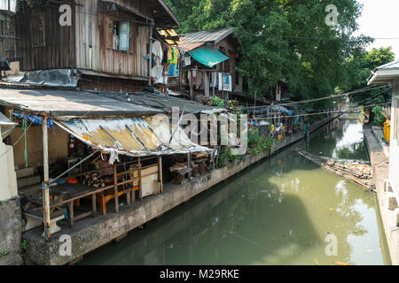 Old typical wooden houses on the Khong Saen Saeb canal in Bangkok - Stock Photo