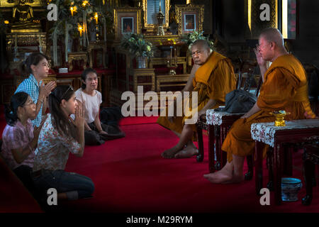 Some faithful in front of the Buddist monks in a temple in Bangkok, Thailand - Stock Photo