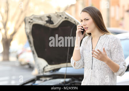 Portrait of an angry woman calling insurance on phone after car breakdown on the street - Stock Photo