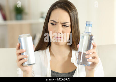 Front view portrait of a confused girl deciding between soda refreshment and water bottle at home - Stock Photo