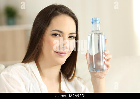 Portrait of a relaxed girl showing a generic water bottle at home - Stock Photo