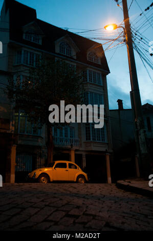 A yellow Volkswagen Beetle illuminated by a streetlight at dusk in La Paz, Bolivia - Stock Photo
