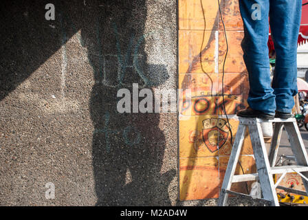 A man standing on a stepladder wearing jeans while repairing wiring - Stock Photo