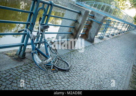 A broken bike is locked to the railing at the river in the city center. The front wheel was stolen. - Stock Photo