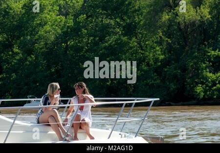 Washington DC - April 30. 2011: Two young women relaxing on the sailing boat in Washington DC - Stock Photo