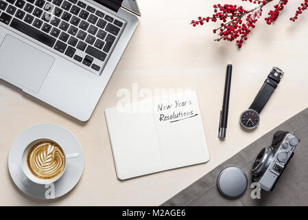 New year's resolutions writing in open notepad with coffee mug, camera, clock and laptop lying on photography office - Stock Photo