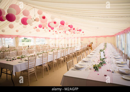 Marquee with tables set for wedding reception, paper lanterns decorating marquee - Stock Photo