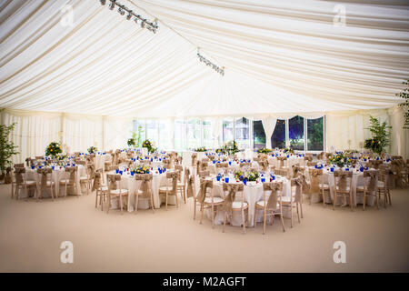 Marquee with tables set for wedding reception - Stock Photo