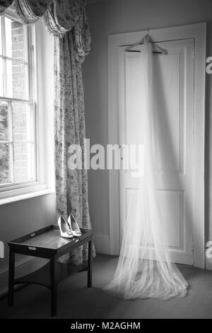 Wedding veil hanging on door and shoes on table, black and white - Stock Photo
