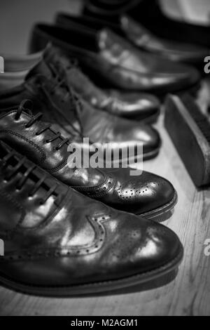 Row of men's shoes with shoe brush, close-up, black and white - Stock Photo
