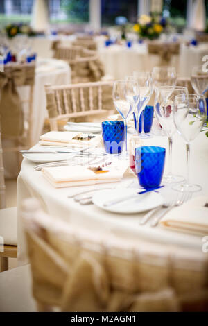 Wedding reception tables with place settings and wine glasses - Stock Photo