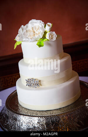 Three tiered white icing wedding cake with iced flower decoration - Stock Photo