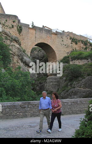 Ronda, Spain - May 2, 2014: Tourist couple walking near Puente Nueve Bridge in Ronda, Spain - Stock Photo