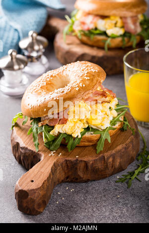 Bagels with scrambled eggs, rucola and fried bacon - Stock Photo