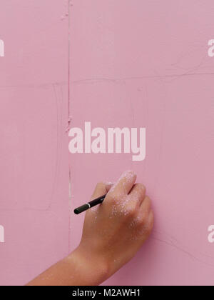 An artist hand with a pencil sketching the art work on the pink wall - Stock Photo