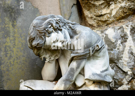 stone sculpture of suffering woman at historical monumental Staglieno Cemetery in town, shot in bright  winter light - Stock Photo
