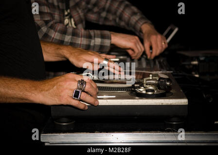 close up of two DJs hands playing vinyls on their record decks at a party in a nightclub - Stock Photo