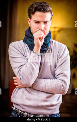 Young man at home sick, coughing - Stock Photo