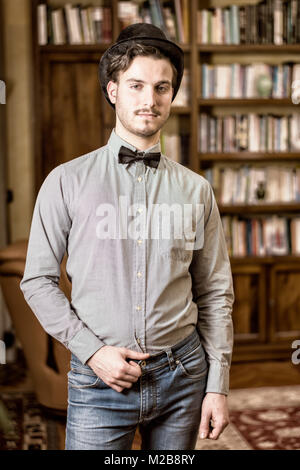Attractive young man wearing top hat and bow tie - Stock Photo