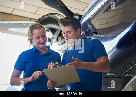 Aero Engineer And Apprentice Working On Helicopter In Hangar - Stock Photo