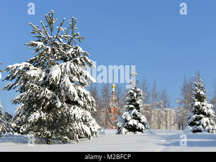 Snow-covered Moscow. Landscaped park after heavy snowfall. Fir-trees in snow against background of church - Stock Photo