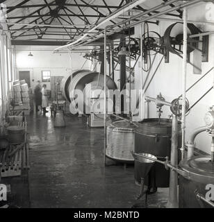 1950s, historical picture of the interior of an industrial creamery in Ireland, showing the dairy processing equipment, - Stock Photo